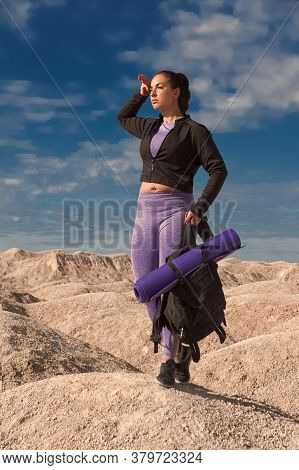 Young Woman Half-face One Tourist On Hill Area In Sportswear And With Backpack Looking Into The Dist