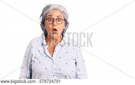 Senior woman with gray hair wearing casual business clothes and glasses scared and amazed with open mouth for surprise, disbelief face