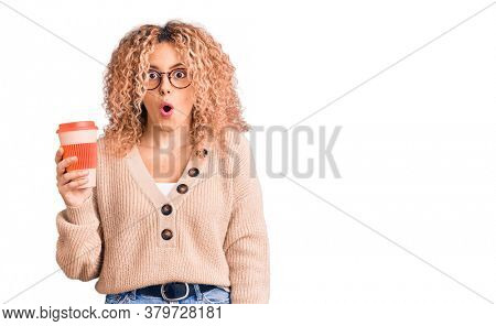 Young blonde woman with curly hair wearing glasses and drinking a cup of coffee scared and amazed with open mouth for surprise, disbelief face