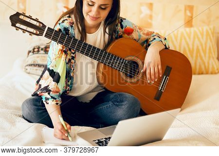 Crop Female Musician With Acoustic Guitar And Laptop Making Notes While Sitting On Bed And Writing S