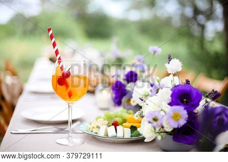 Glass Of Delicious Aperol Spritz Drink With Straw Placed On Banquet Table With Appetizers And Fresh