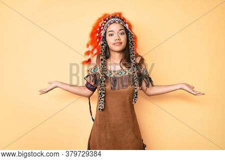 Young beautiful latin girl wearing indian costume clueless and confused expression with arms and hands raised. doubt concept.