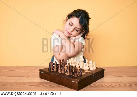 Cute hispanic child playing chess sitting on the table hugging oneself happy and positive, smiling confident. self love and self care