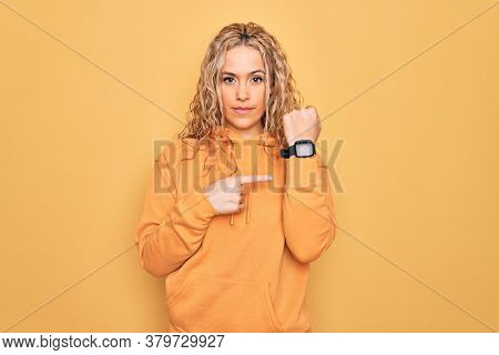 Young beautiful blonde sporty woman wearing casual sweatshirt over yellow background In hurry pointing to watch time, impatience, looking at the camera with relaxed expression