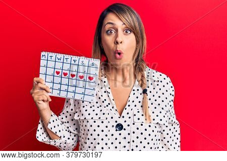Young beautiful woman holding period calendar scared and amazed with open mouth for surprise, disbelief face