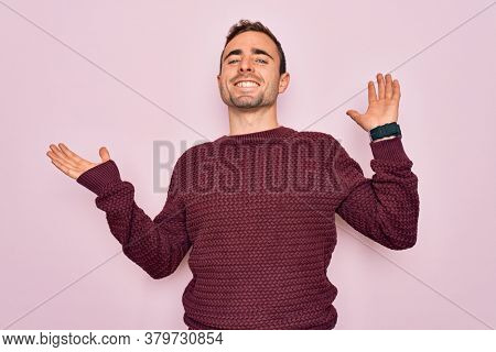 Young handsome man with blue eyes wearing casual sweater standing over pink background clueless and confused expression with arms and hands raised. Doubt concept.