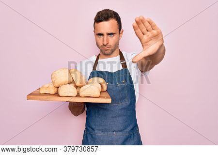 Young handsome baker man with blue eyes wearing apron holding tray with homemade bread with open hand doing stop sign with serious and confident expression, defense gesture