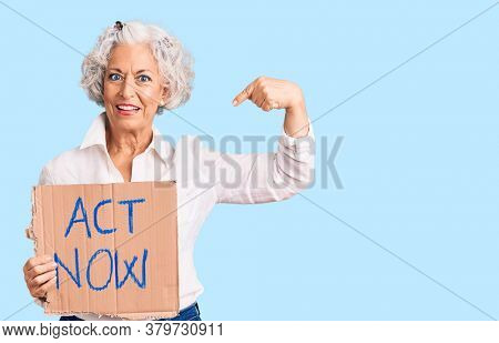 Senior grey-haired woman holding act now banner pointing finger to one self smiling happy and proud