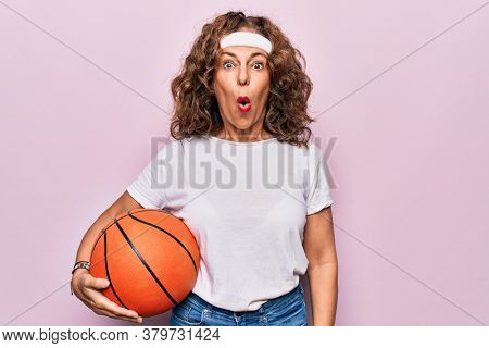 Middle age brunette basketball player woman holding game ball over isolated pink background scared and amazed with open mouth for surprise, disbelief face