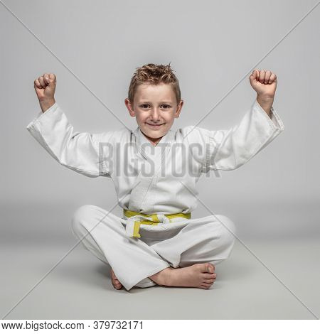 cheerful child practicing martial arts sitting on the ground with his arms raised in a sense of victory. happy expression.