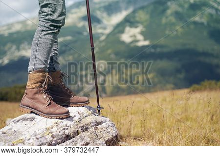 Closeup Detail Of Woman With Brown Leather Boots And Hiking Stick Standing On A Rock With Mountains
