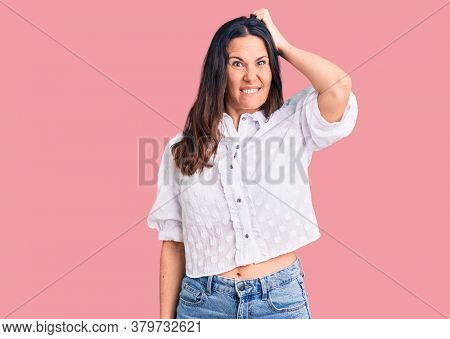 Young beautiful brunette woman wearing casual shirt confuse and wonder about question. uncertain with doubt, thinking with hand on head. pensive concept.