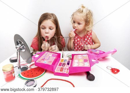 Childrens Cosmetics: Two Little Girls Show Off At The Mirror And Paint Their Lips.