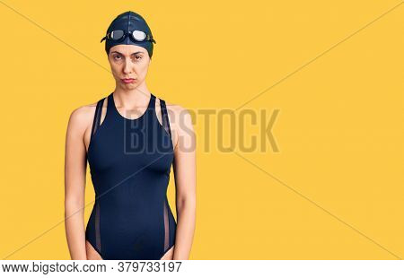 Young beautiful hispanic woman wearing swimwear and swimmer glasses skeptic and nervous, frowning upset because of problem. negative person.