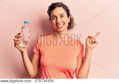 Young beautiful hispanic woman drinking bottle of water smiling happy pointing with hand and finger to the side