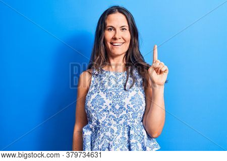 Young beautiful brunette woman wearing casual sleeveless t-shirt over blue background smiling with an idea or question pointing finger up with happy face, number one