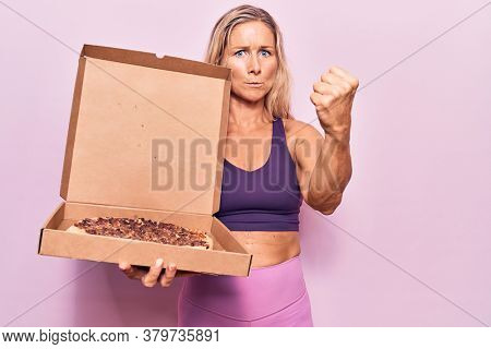 Middle age caucasian blonde woman wearing workout clothes and holding pizza box annoyed and frustrated shouting with anger, yelling crazy with anger and hand raised