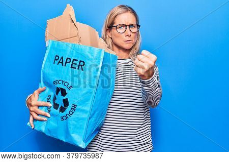 Middle age caucasian blonde woman holding recycling wastebasket with paper and cardboard annoyed and frustrated shouting with anger, yelling crazy with anger and hand raised