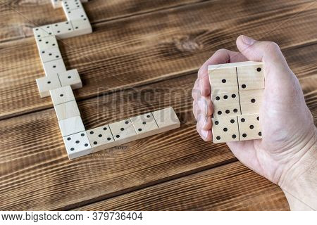 Domino. A Human Hand With A Domino. A Game Of Dominoes On A Wooden Table