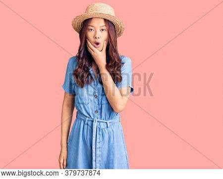 Young beautiful chinese girl wearing summer hat looking fascinated with disbelief, surprise and amazed expression with hands on chin