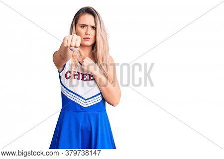 Young beautiful blonde woman wearing cheerleader uniform punching fist to fight, aggressive and angry attack, threat and violence