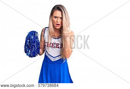 Young beautiful blonde woman wearing cheerleader uniform holding pompom annoyed and frustrated shouting with anger, yelling crazy with anger and hand raised