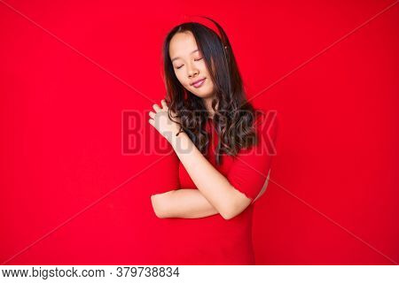 Young beautiful chinese girl wearing casual clothes hugging oneself happy and positive, smiling confident. self love and self care