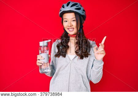 Young beautiful chinese girl wearing bike helmet and holding water bottle smiling happy pointing with hand and finger to the side