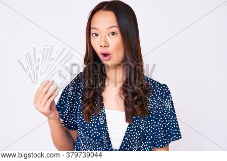 Young beautiful chinese girl holding dollars scared and amazed with open mouth for surprise, disbelief face