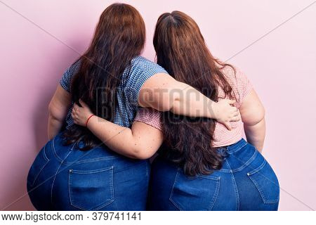 Young plus size twins wearing casual clothes hugging oneself happy and positive from backwards. self love and self care