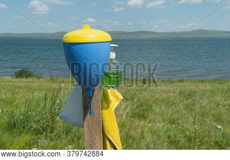 Hand Washbasin On The Shore Of A Beautiful Lake. Selective Focus. Concept Of Outdoor Recreation And