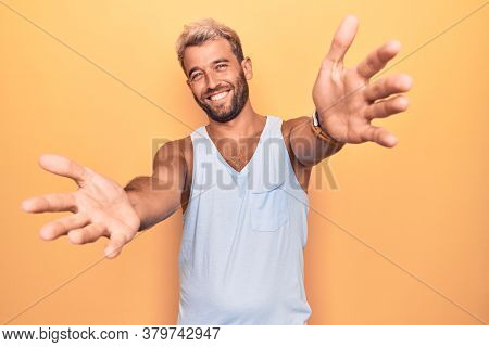 Young handsome blond man wearing casual sleeveless t-shirt over isolated yellow background looking at the camera smiling with open arms for hug. Cheerful expression embracing happiness.