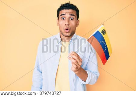 Young handsome hispanic man holding venezuelan flag scared and amazed with open mouth for surprise, disbelief face
