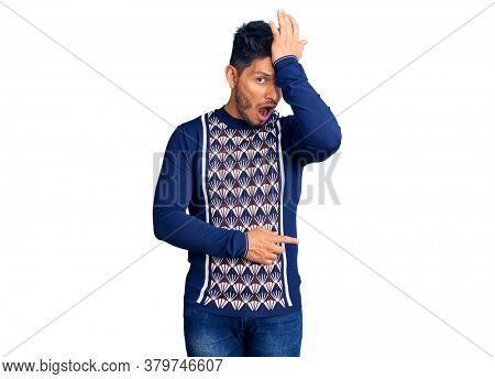 Handsome latin american young man wearing casual winter sweater surprised with hand on head for mistake, remember error. forgot, bad memory concept.