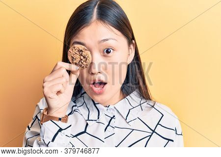 Young beautiful chinese woman holding cookie over eye scared and amazed with open mouth for surprise, disbelief face