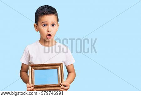 Little cute boy kid holding empty frame scared and amazed with open mouth for surprise, disbelief face