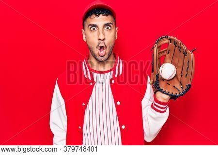 Young hispanic man wearing baseball uniform holding golve and ball scared and amazed with open mouth for surprise, disbelief face