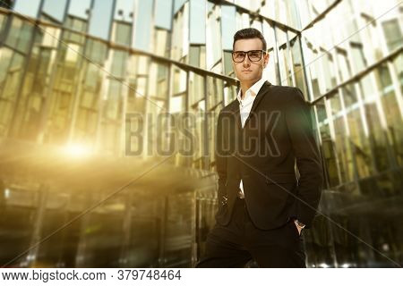 A portrait of a goodlooking young guy on the background of a mirrored building. Men's beauty, fashion, business.