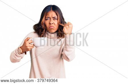Young beautiful mixed race woman holding a cup of coffee annoyed and frustrated shouting with anger, yelling crazy with anger and hand raised