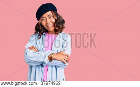 Young beautiful mixed race woman wearing french look with beret happy face smiling with crossed arms looking at the camera. positive person.