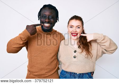 Interracial couple wearing casual clothes smiling cheerful showing and pointing with fingers teeth and mouth. dental health concept.