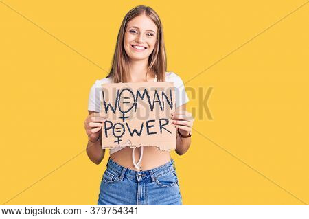Young beautiful blonde woman holding woman power banner looking positive and happy standing and smiling with a confident smile showing teeth