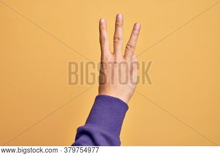 Hand of caucasian young man showing fingers over isolated yellow background counting number 3 showing three fingers