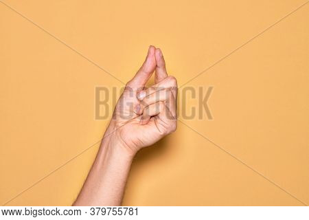 Hand of caucasian young man showing fingers over isolated yellow background holding blank space with thumb finger, business and advertising