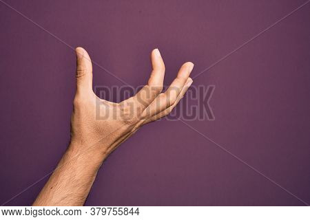 Hand of caucasian young man showing fingers over isolated purple background picking and taking invisible thing, holding object with fingers showing space