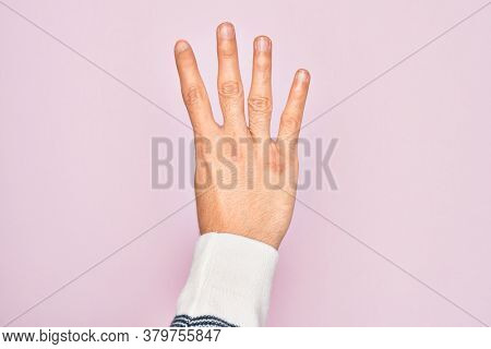 Hand of caucasian young man showing fingers over isolated pink background counting number 4 showing four fingers