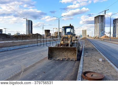 Wheel Loader With A Bucket On A Street In The City During The Construction Of The Road. Construction