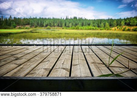 Wooden Pier With Planks At An Idyllic Lake In The Summer With Reeds Growing On The Stage