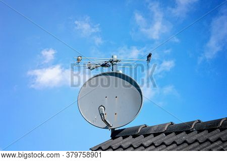 Birds On A Satellite Dish On A Rooftop In The Summer With A Blue Sky
