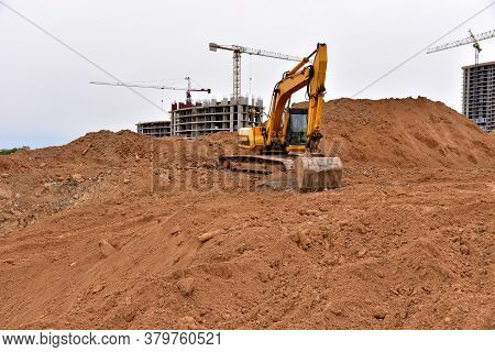 Excavators On Earthworks At Construction Site. Backhoe Digs A Pit For The Construction Of The Road.